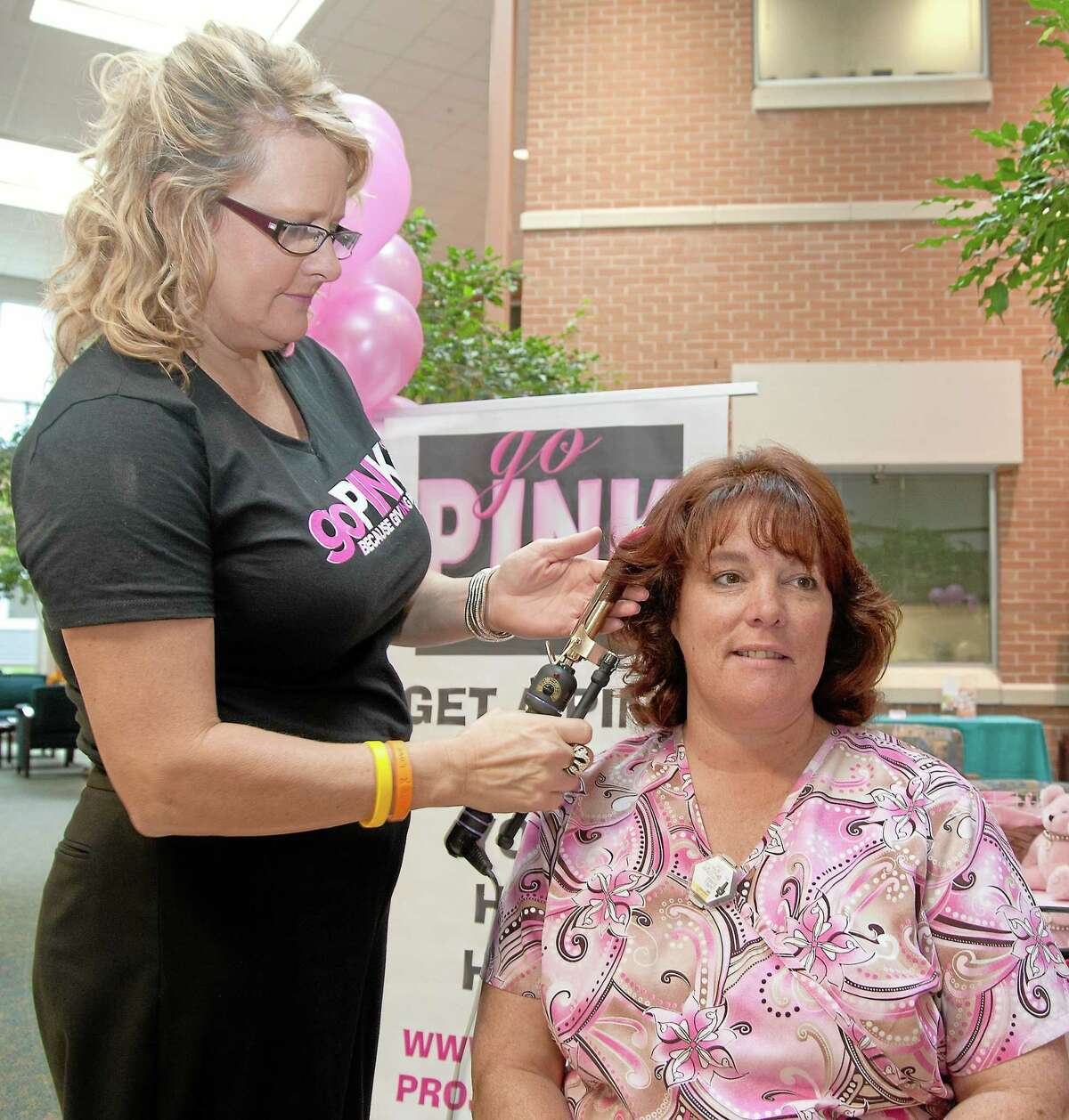 Georgi Marino, left, co-owner of EG Salon, puts the finishing touches on a pink hair extension for Middlesex Hospital Outpatient Center mammography technologist, Laura Daniels, in this archive photograph.
