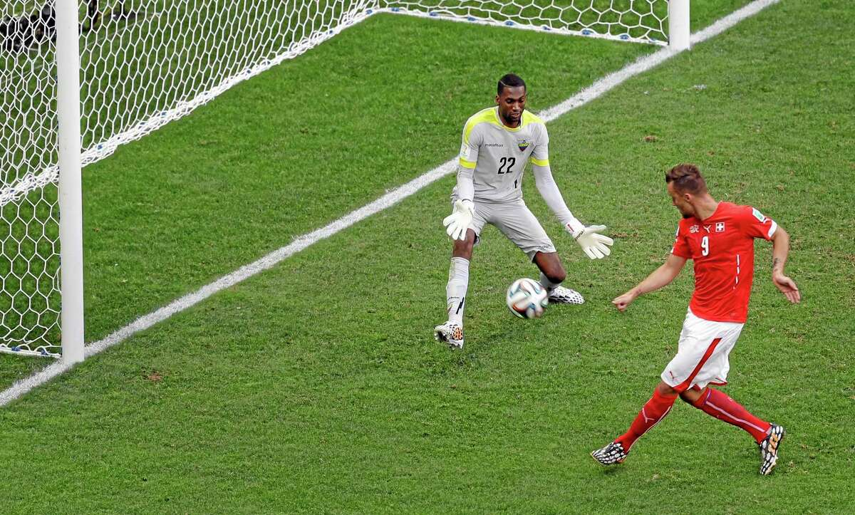 Switzerland's Haris Seferovic, right, scores his side's second goal past Ecuador's goalkeeper Alexander Dominguez on Sunday.