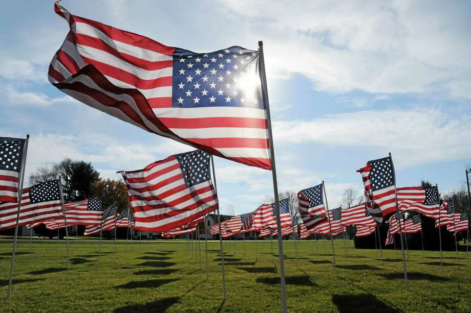 American flags wave in the wind in honor of Veterans Day Sunday, Nov. 11, 2012, at Peace Lutheran Church in St. Joseph, Mich . Photo: AP / THE HERALD-PALLADIUM