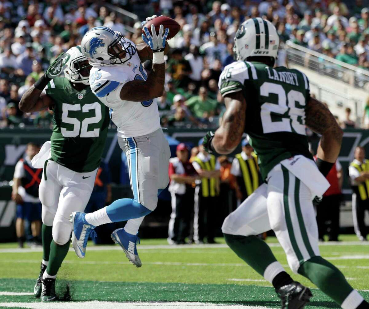 Detroit Lions tight end Eric Ebron, center, pulls in a touchdown reception as New York Jets linebacker David Harris (52) and strong safety Dawan Landry (26) defend on Sept. 28 in East Rutherford, N.J.