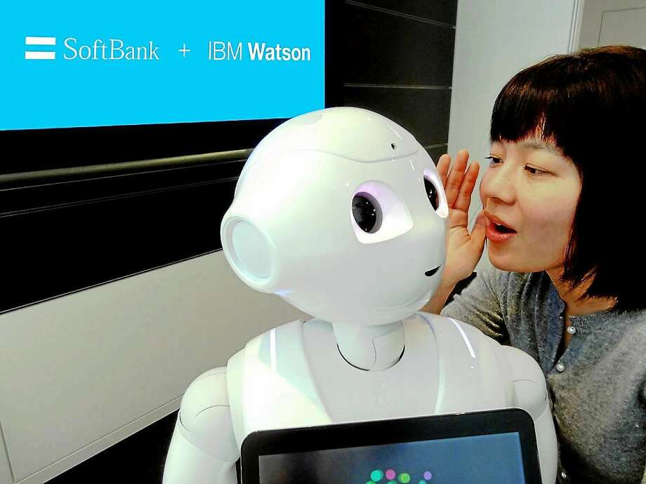 "IBM Researcher Risa Nishiyama demonstrates SoftBank's Pepper robot, which uses the Watson computer. Watson, best known for winning a ""Jeopardy!"" match in 2011, is designed to take in huge amounts of information, process and learn from them in the same way the human brain does. Researchers now are working to teach Watson Japanese. (Courtesy of IBM) Photo: The Washington Post / THE WASHINGTON POST"