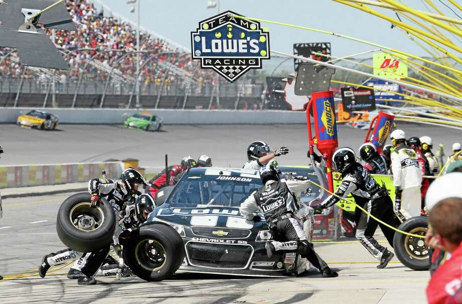 Jimmie Johnson makes a pit stop during the NASCAR Quicken Loans 400 at Michigan International Speedway on Sunday. Photo: Bob Brodbeck — The Associated Press  / FR3471 AP