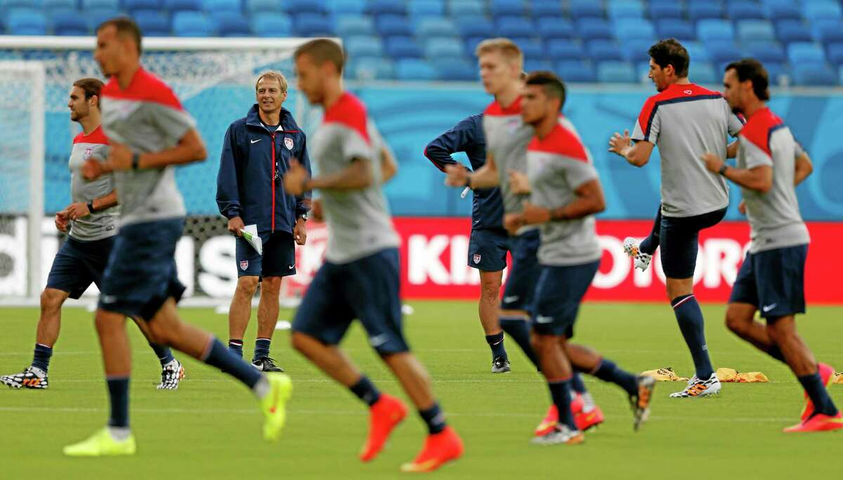 United States' head coach Jurgen Klinsmann, back left, looks on as his team warms up during an official training session Sunday in Brazil.