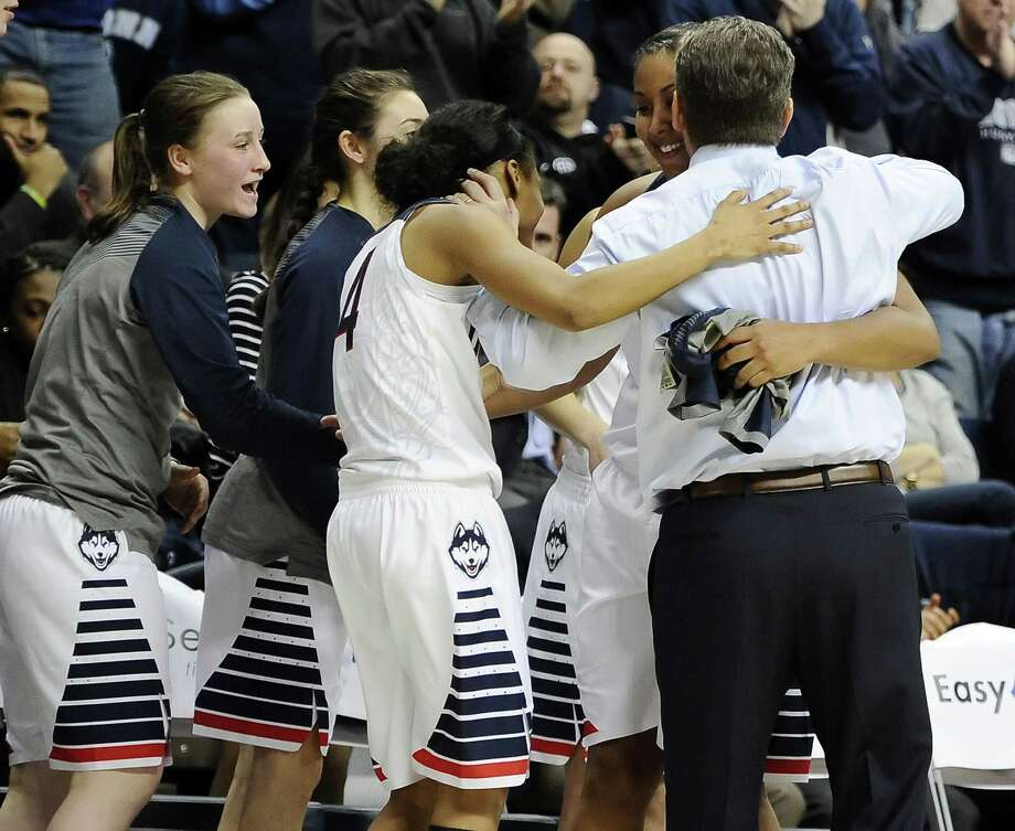 UConn coach Geno Auriemma embraces Moriah Jefferson, left, and Kaleena Mosqueda-Lewis as Tierney Lawlor, far left, and Briana Pulido, second from left, look on late in the second-ranked Huskies' 87-62 win over No. 1 South Carolina on Monday in Storrs. Photo: Jessica Hill — The Associated Press  / FR125654 AP