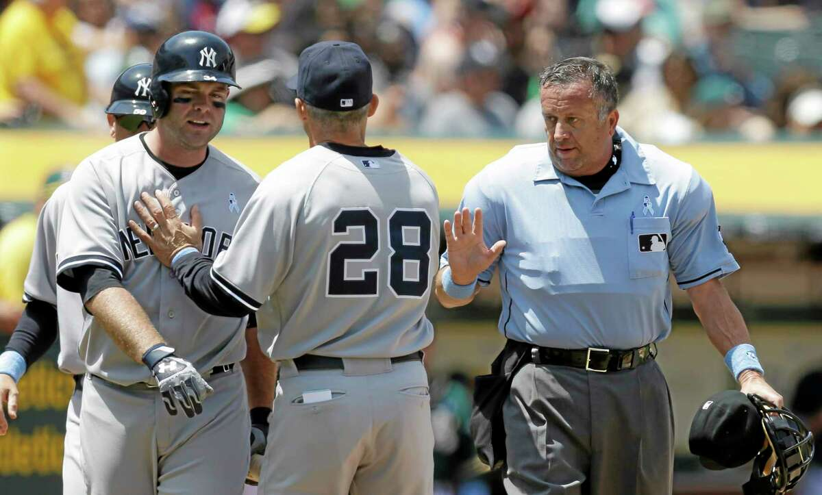 The Yankees' Brian McCann, left, is separated from home plate umpire Dale Scott, right, by manager Joe Girardi (28) in the fourth inning Sunday.