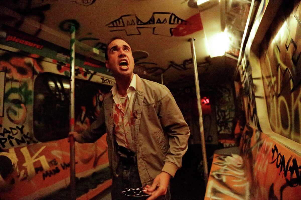 In this Oct. 2, 2014 photo, an actor performs during ìNightmare: New York,î a haunted house attraction in New York. The ìNightmareî Lower East Side house transports visitors to the cityís ìbad old days,î including the demented rat-and-crime infested subway of the 1980s. (AP Photo/Frank Franklin II)