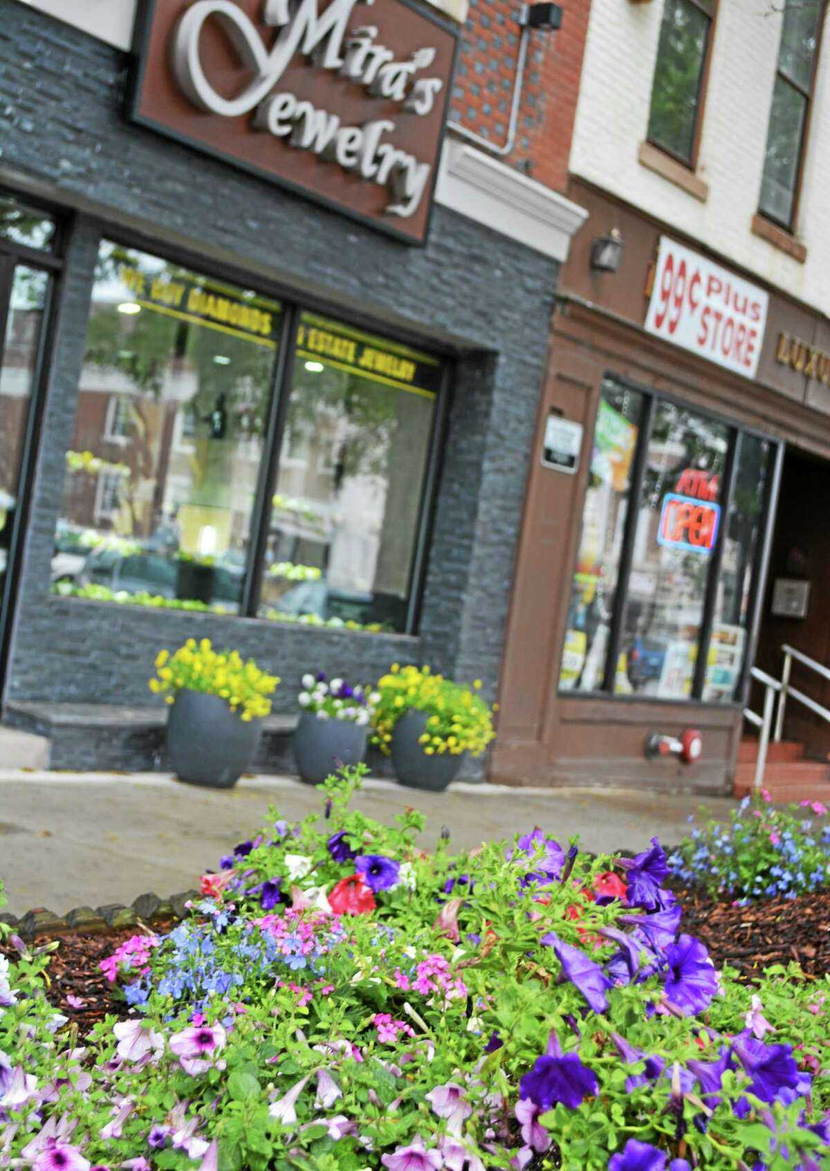 The sidewalk in front of Mira Jewelry in Middletown is enhanced by the planting of pink and green flowers.
