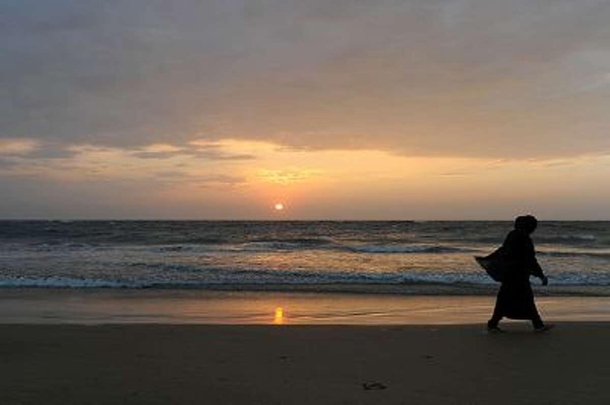 A Sri Lankan beachgoer walks during sunset in Colombo on January 30, 2014. Sri Lanka's youth population aged 10 to 19 make up some 15 percent of its 20 million people. AFP PHOTO/ LAKRUWAN WANNIARACHCHI (Photo credit should read LAKRUWAN WANNIARACHCHI/AFP/Getty Images)