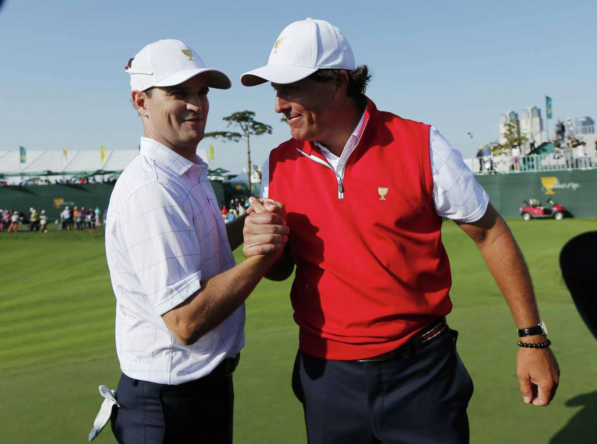 The United States' Phil Mickelson, right, shakes hands with partner Zach Johnson after they won their their foursome match Thursday at the Presidents Cup at the Jack Nicklaus Golf Club Korea in Incheon, South Korea.