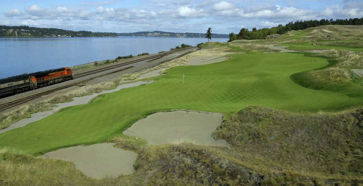 The 16th hole of the Chambers Bay golf course is shown as a freight train passes at left in University Place, Wash.