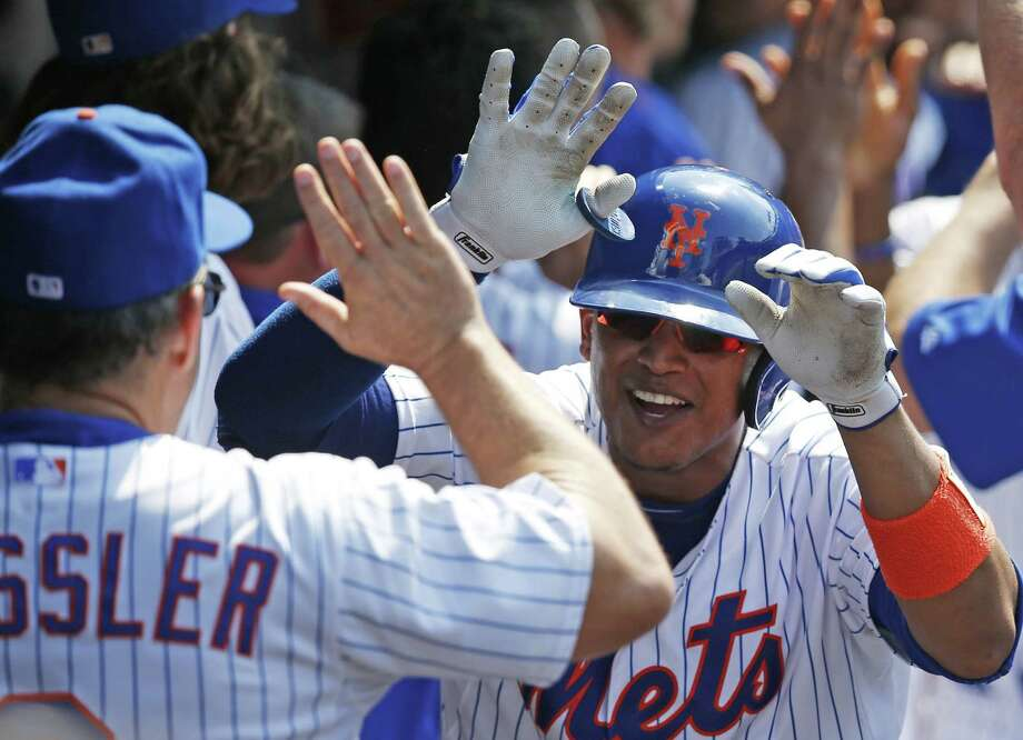 Mets assistant hitting coach Pat Roessler (6) congratulates Juan Lagares after Lagares hit a sixth-inning, three-run home run on Sunday. Photo: Kathy Willens — The Associated Press  / AP