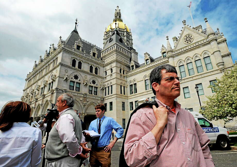 Larry Dorman, the chief spokesman for The State Employees Bargaining Agent Coalition (SEBAC), right, stands off to the side as Leo Canty, second vice president of the American Federation of Teachers, left, speaks to the media outside the state Capitol in Hartford, Conn. on  May 10, 2011. Photo: AP Photo/Jessica Hill  / FR125654 AP
