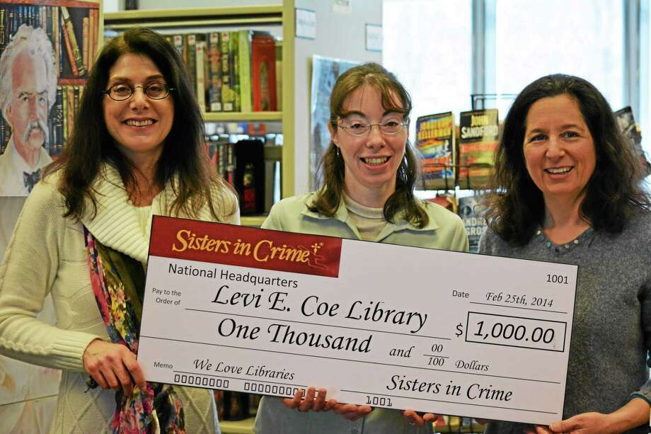 "(Left to right) Levi E. Coe Library staff members Loren Webber, Susan Mizla and Vicki Berry hold a $1,000 check presented by the New England chapter of ""Sisters in Crime."" The Middlefield library was the recipient of the prize during the ""Sisters in Crime"" monthly ""We Love Libraries"" lottery drawing earlier this week. Photo: Submitted Photo."