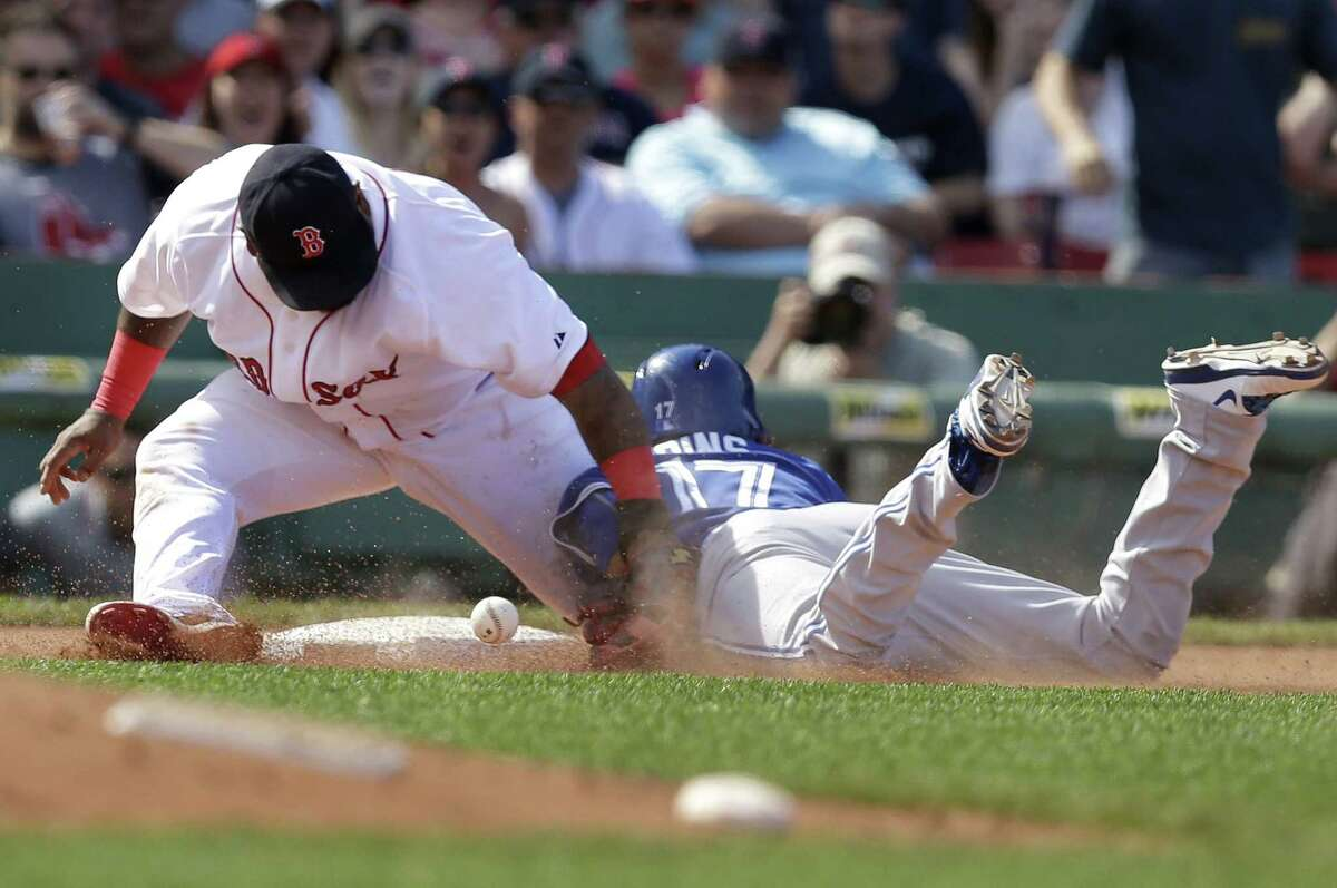 Pablo Sandoval, left, is unable to tag the Blue Jays' Ryan Goins, right, in the seventh inning Sunday at Fenway Park.