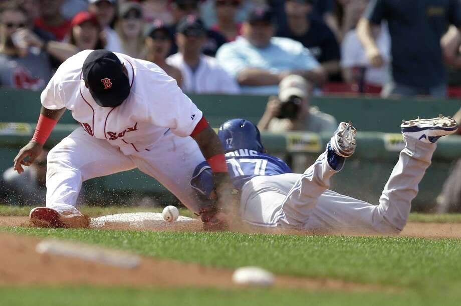 Pablo Sandoval, left, is unable to tag the Blue Jays' Ryan Goins, right, in the seventh inning Sunday at Fenway Park. Photo: Steven Senne — The Associated Press  / AP