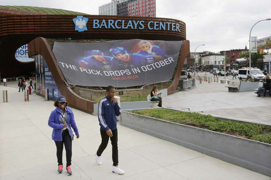 People walk by the Barclays Center on Thursday in Brooklyn. The New York Islanders, who formerly played at Nassau Coliseum in Uniondale, will now call Brooklyn home when they open the 2015-2016 season. Photo: Mark Lennihan — The Associated Press  / AP