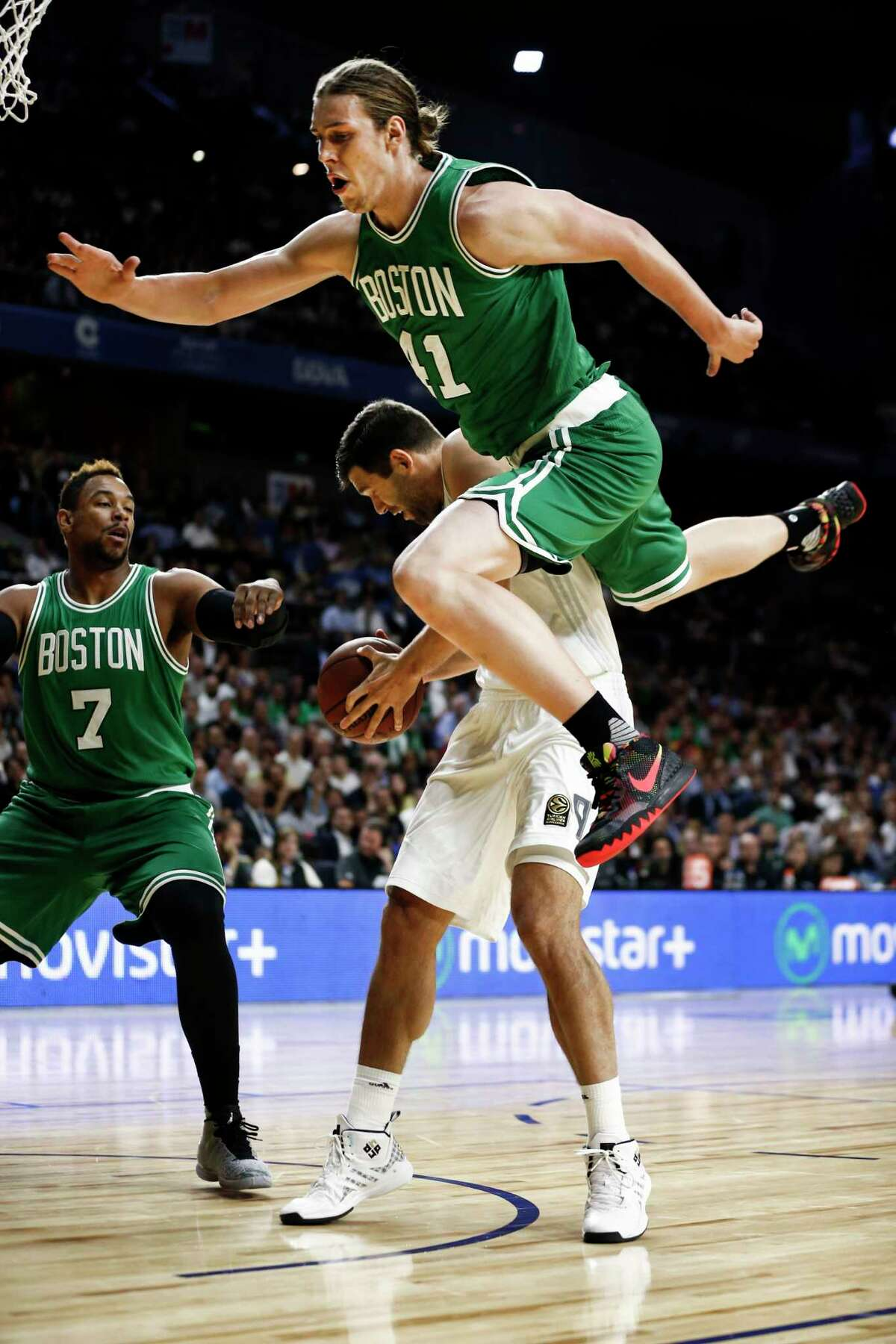The Boston Celtics' Kelly Olynyk, top, falls over Real Madrid's Felipe Reyesd during Thursday's game against Real Madrid at the Barclaycard Centre sport arena in Madrid, Spain.
