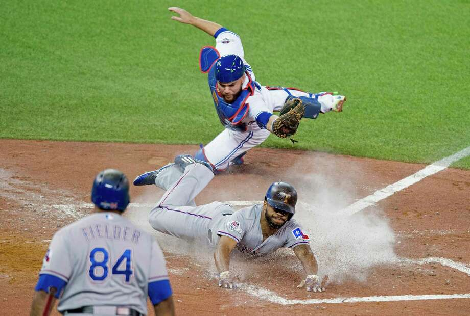 The Rangers' Delino DeShields, center, scores past  Blue Jays catcher Russell Martin during the third inning of Game 1 of the American League Division Series on Thursday. Photo: Darren Calabrese — The Canadian Press Via AP  / CP