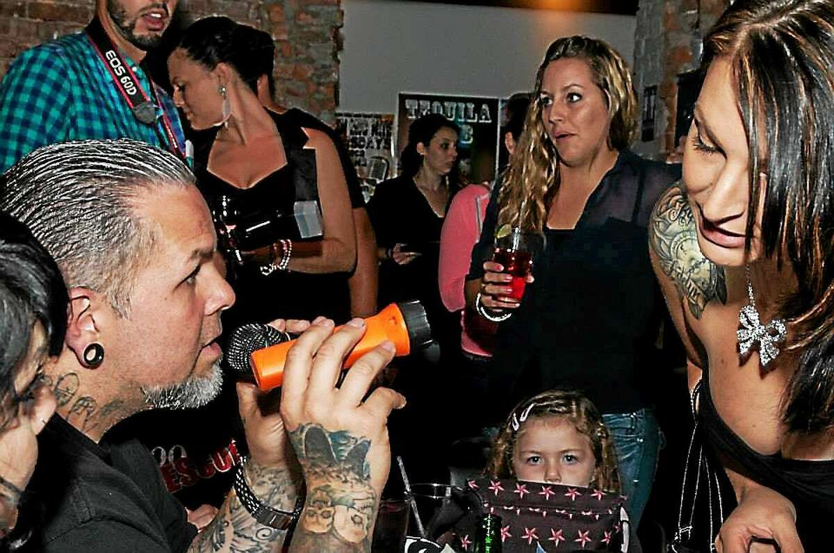 """Joey Tattoo, host of the show """"Tattoo Rescue"""" on Spike TV, is shown judging contestants at last year's Tattoo Peep Show at La Boca Restaurant and Cantina in Middletown. His daughter is at center."""