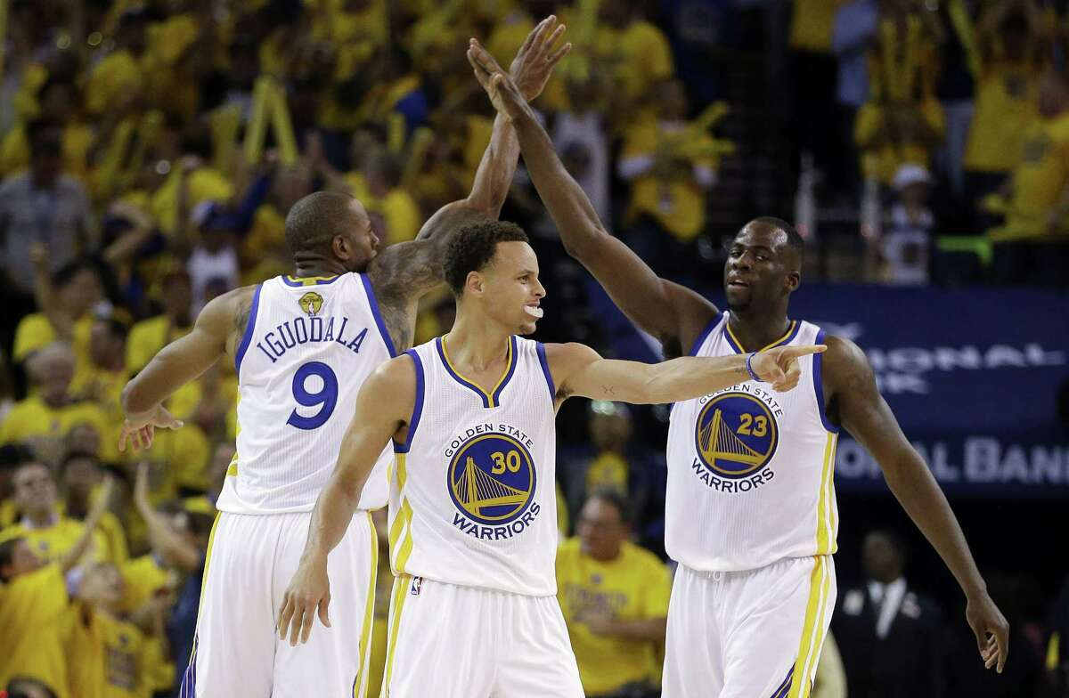 Warriors guard Stephen Curry, center, forward Andre Iguodala, left, and forward Draymond Green react during the second half of Game 5 of the NBA Finals on Sunday.