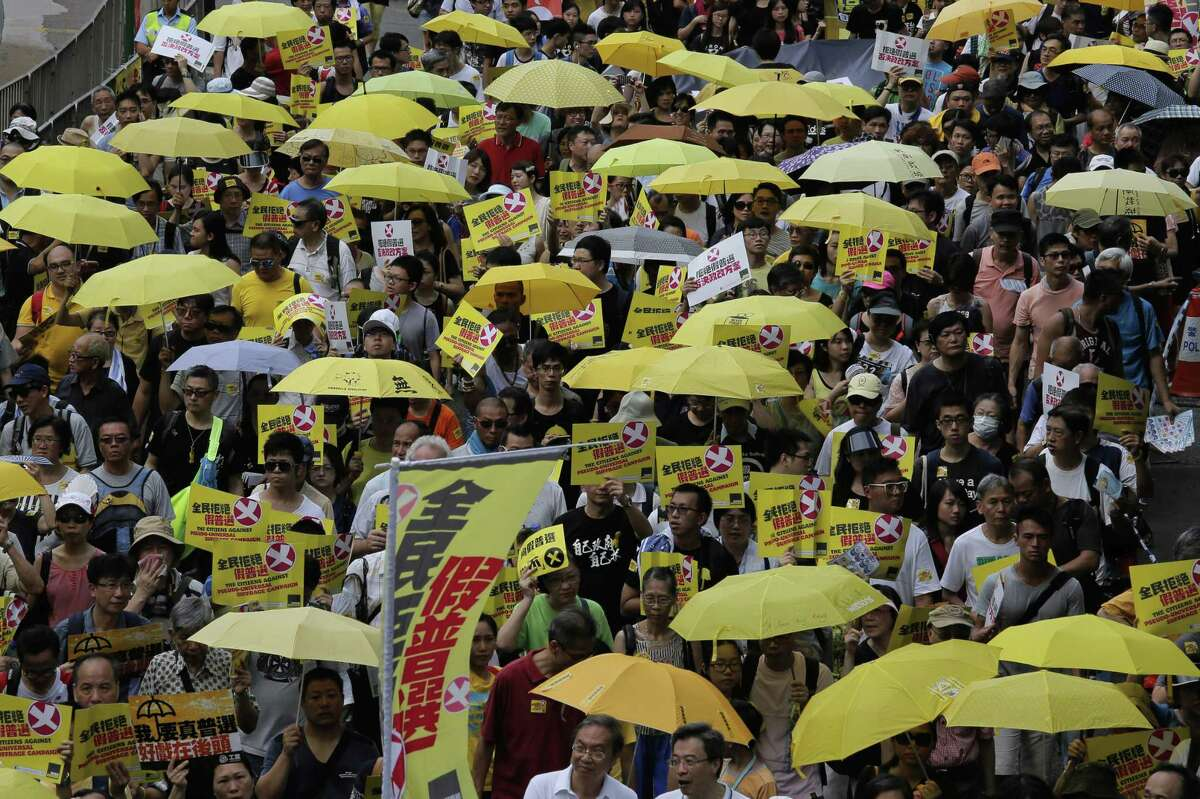 Protesters carry yellow umbrellas during a rally as people march in a downtown street to support a veto of the government's electoral reform package in Hong Kong on June 14, 2015. The rally was held ahead of a crucial vote by lawmakers on Beijing-backed election reforms that sparked huge street protests last year.