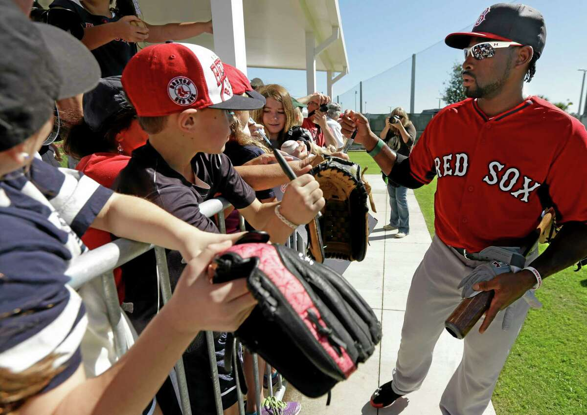 Boston Red Sox center fielder Jackie Bradley Jr. signs autographs for fans during practice on Feb. 17 in Fort Myers, Fla.