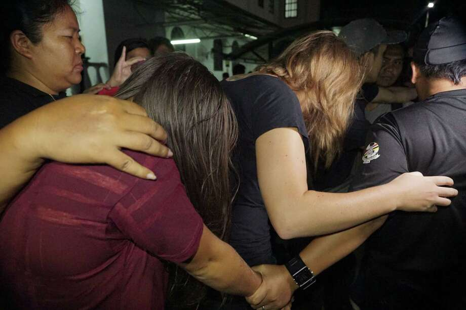 Canadian Danielle Petersen, 22, center right, and left, Eleanor Hawkins, 24, left, of Britain are escorted by police as they leave court in Kota Kinabalu, in eastern Sabah state on Borneo island, Malaysia, on June 12, 2015. Both women were among 10 people who stripped naked and took photos on Mount Kinabalu on May 30. Photo: AP Photo/Mohd Asraffirdauz Bin Abdullah  / AP