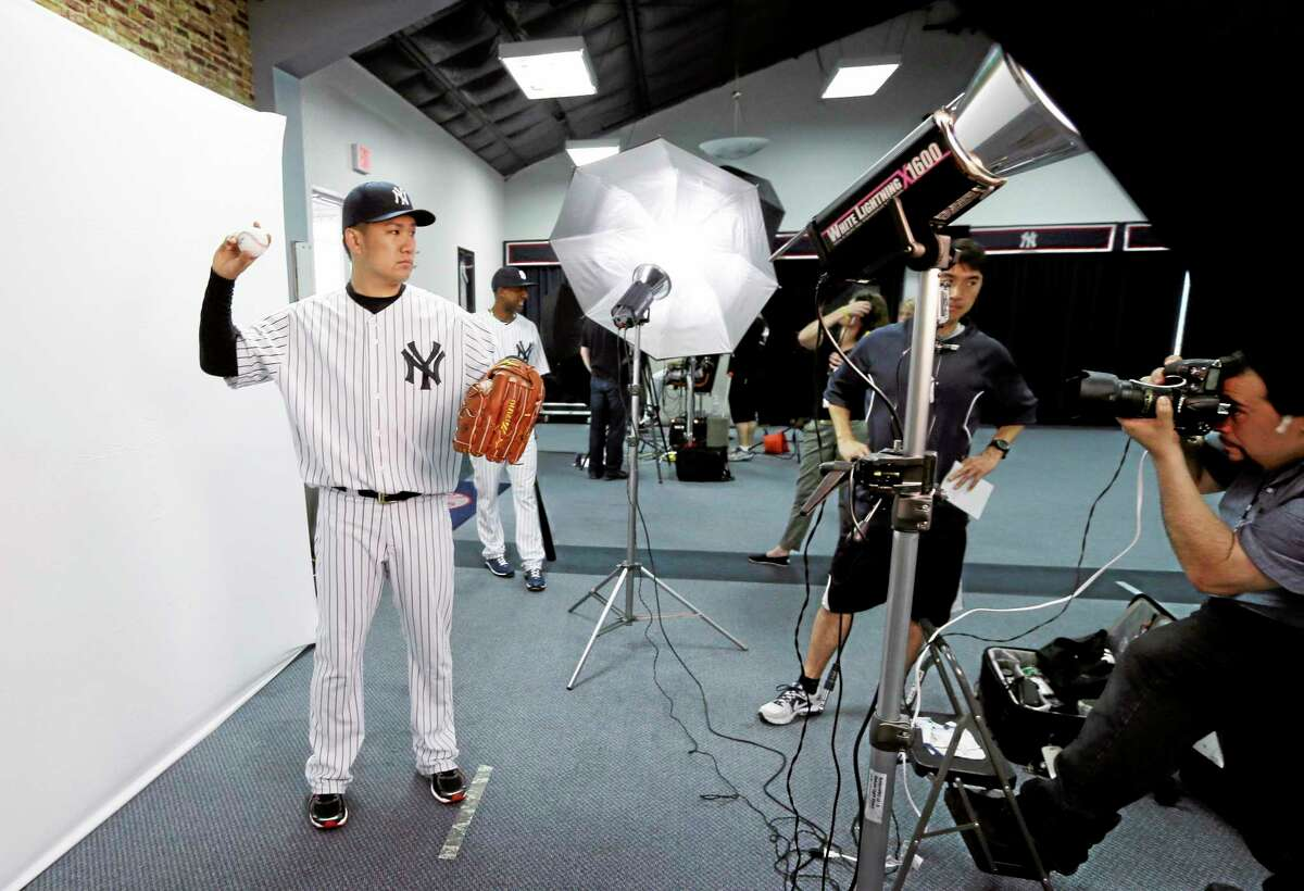 New York Yankees starter Masahiro Tanaka poses during the Yankees' photo day before a practice on Saturday in Tampa, Fla.