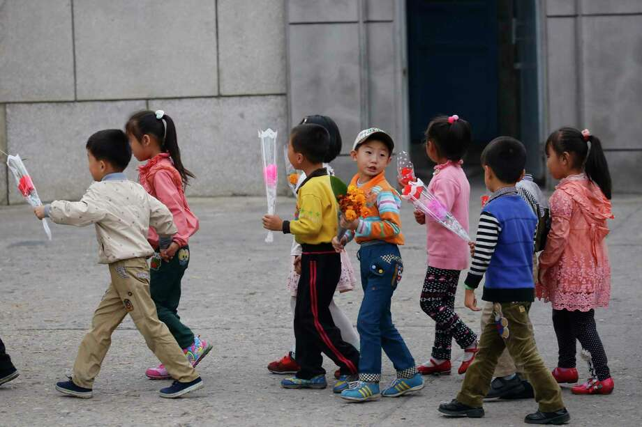 Children walk with decorative flowers for the upcoming anniversary celebrations in Pyongyang, North Korea, Thursday, Oct. 8, 2015. The country is in high gear with preparations for the 70th anniversary of the founding of the North Korea Workers' Party on Oct. 10, 2015. Photo: AP Photo/Charles Dharapak   / AP