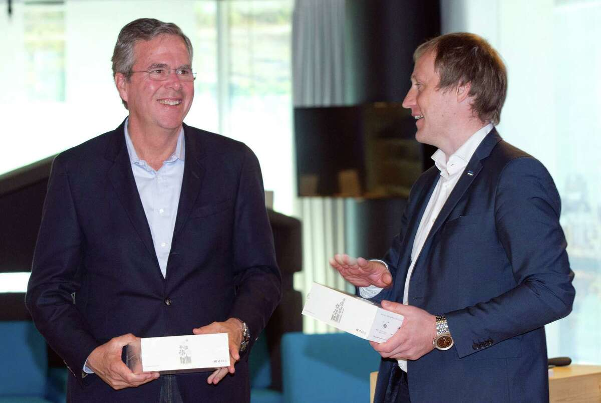 Former Florida Gov. Jeb Bush, left, smiles while listening to Taavi Kotka, Deputy Secretary General - ICT at Ministry of Economic Affairs and Communications for Estonia at the e- Estonia Showroom during his visit in Tallinn, Estonia on June 13, 2015.