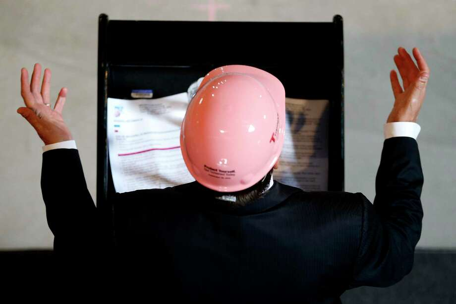 Supporters of breast cancer awareness wear pink hardhats while forming a ribbon at a construction site, Wednesday, Sept. 30, 2015, in Fort Lee, N.J. EMCOR, which provides mechanical and electrical construction services, presented a $50,000 donation to the John Theurer Cancer Center Breast Oncology Division at Hackensack University Medical Center during the event. Photo: AP Photo/Julio Cortez   / AP