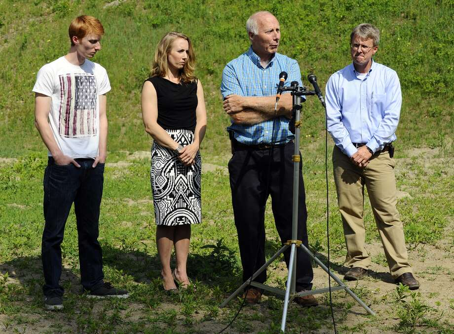 On Thursday, June 11, 2015 in Bolton, Mass., David Broomfield, 25, far left, Corinne Maleski and Andrew Broomfield, 38, stand next to their father, Thomas Broomfield, as he speaks about the recent death of his son, Keith Broomfield, who died while fighting with Kurdish forces against the Islamic State in Syria. Photo: Christine Hochkeppel/Worcester Telegram & Gazette Via AP  / Worcester Telegram & Gazette