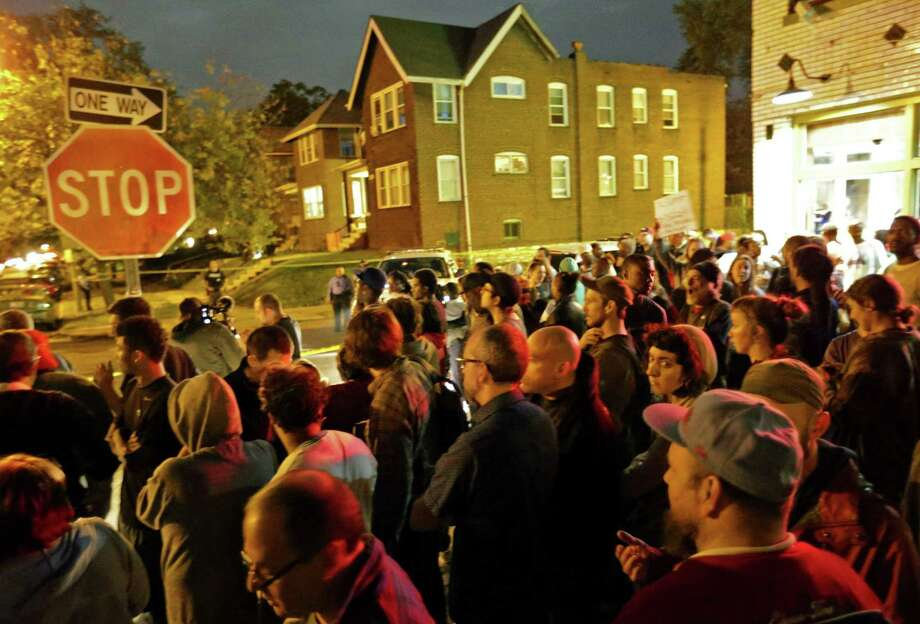 A crowd gathers near the scene in the 4100 block of Shaw Boulevard where a man was fatally shot by an off-duty St. Louis police officer on Wednesday, Oct. 8, 2014. St. Louis Police Lt. Col. Alfred Adkins said the 32-year-old officer was working a secondary security job late Wednesday when the shooting happened. (AP Photo/St. Louis Post-Dispatch, David Carson) Photo: AP / St. Louis Post-Dispatch