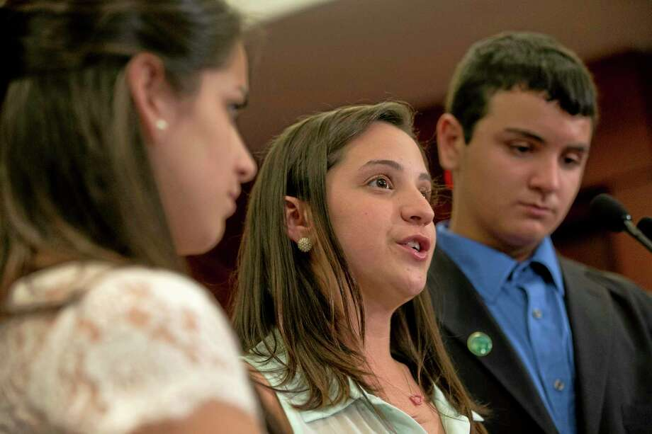 Jillian Soto, center, with siblings Carlee Soto, left and Carlos Soto, the siblings of Victoria Soto, speaks during a news conference on Capitol Hill in Washington, Thursday, June 13, 2013, on the sixth month anniversary of the Newtown, Conn. shootings. (AP Photo/Jacquelyn Martin) Photo: AP / AP