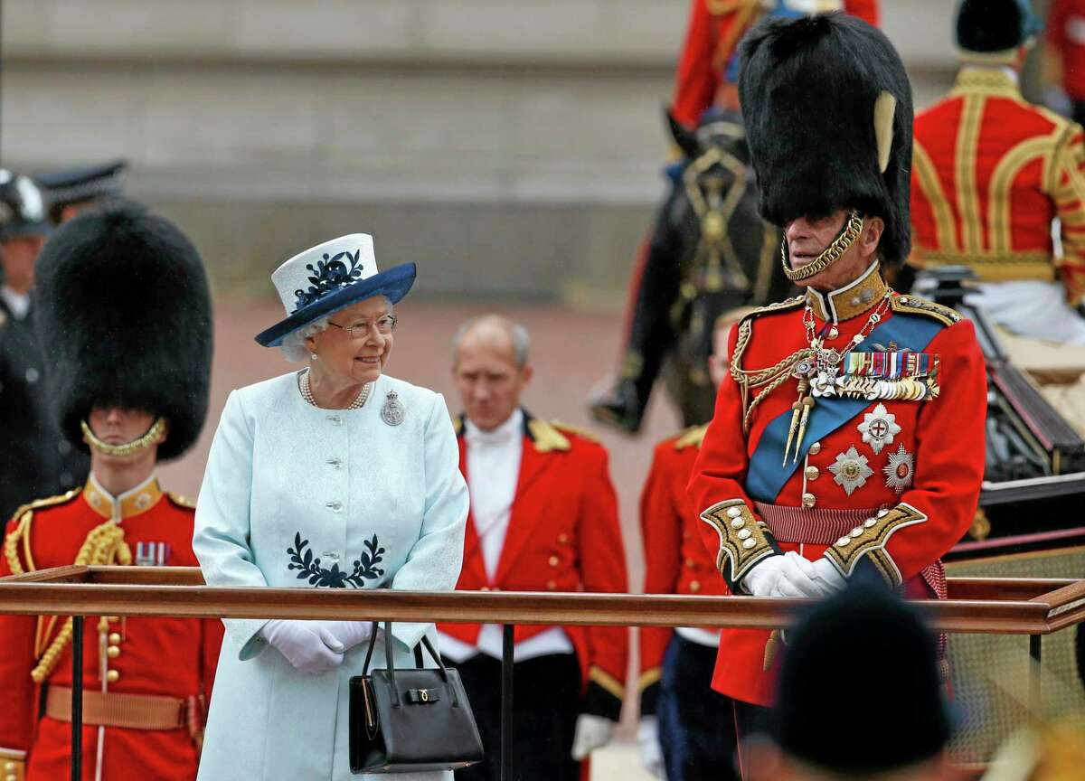 Britain's Queen Elizabeth II, left, along with Prince Philip, wait to review parading troops during the Trooping The Colour parade, outside Buckingham Palace in central London, Saturday, June 14, 2014. Hundreds of soldiers in ceremonial dress have marched in London in the annual