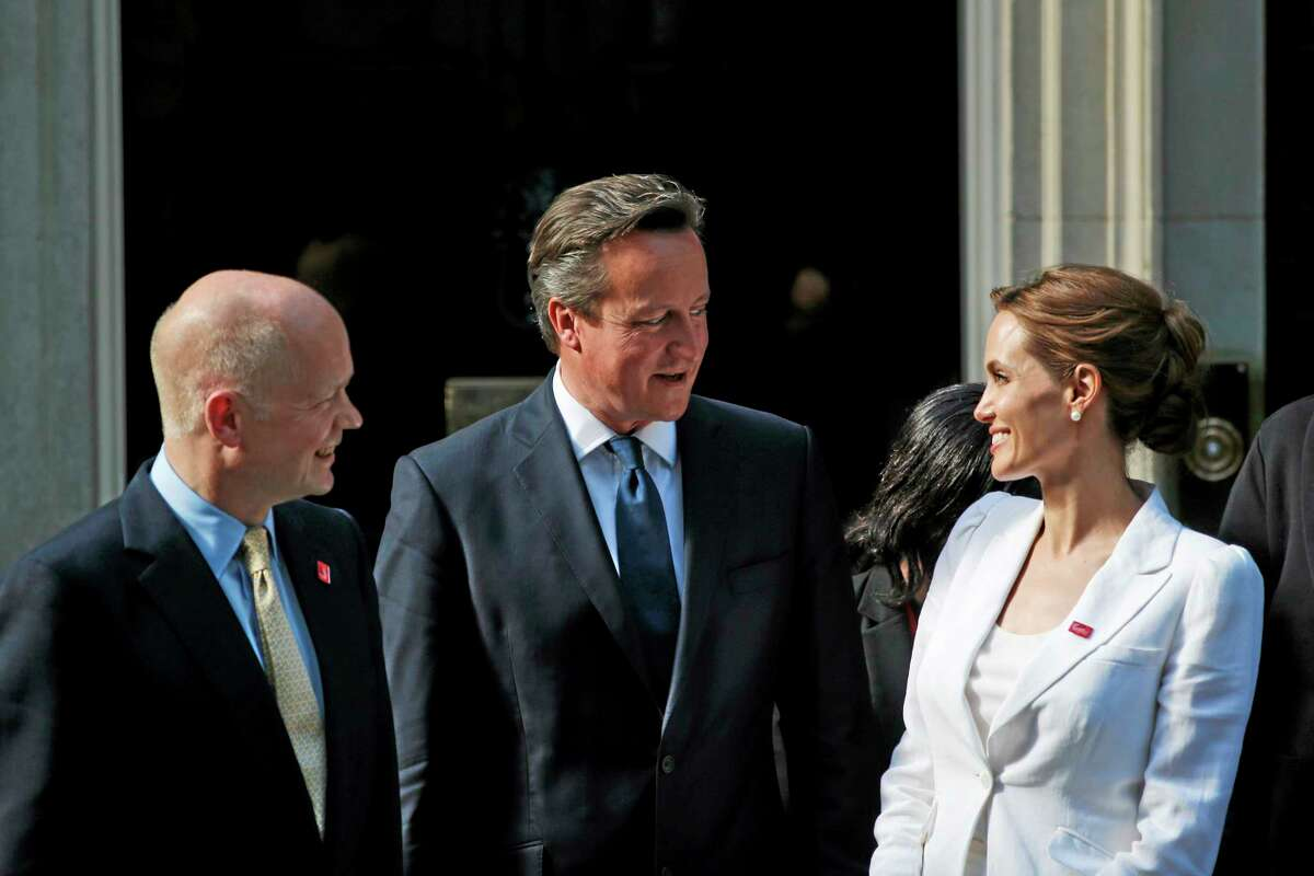 British Prime Minister David Cameron, centre, talks with U.S actress Angelina Jolie, Special Envoy of the United Nations High Commissioner for Refugees, right, and Britain's Foreign Secretary William Hague, left, as they pose for the photographers on the doorstep of Cameron's official residence at 10 Downing Street, following their meeting in central London, Tuesday, June 10, 2014. Hague and Jolie opened the Global Summit to End Sexual Violence in Conflict Tuesday. The Summit will welcome governments from over 100 countries, over 900 experts, NGOs, Faith leaders, and representatives from international organisations across the world. It is the biggest ever international meeting on this issue. (AP Photo/Lefteris Pitarakis)