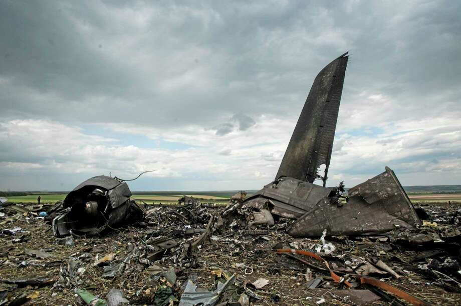 Remnants of a downed Ukrainian army aircraft Il-76 at the airport near Luhansk, Ukraine, Saturday, June 14, 2014. Pro-Russian separatists shot down the military transport plane Saturday in the countryís restive east, killing all 49 service personnel on board, Ukrainian officials said. (AP Photo/Evgeniy Maloletka) Photo: AP / AP