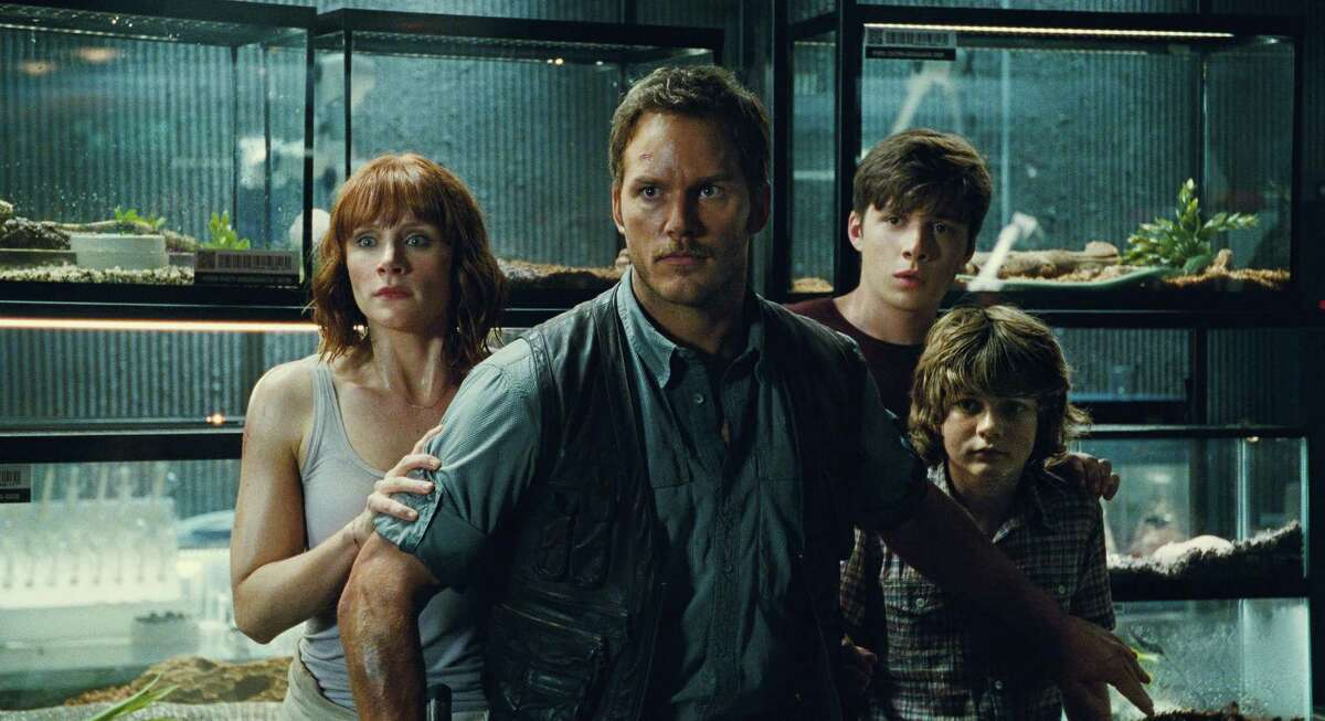 """This photo provided by Universal Pictures shows, Bryce Dallas Howard, from left, as Claire, Chris Pratt as Owen, Nick Robinson as Zach, and Ty Simpkins as Gray, in a scene from the film, """"Jurassic World,"""" directed by Colin Trevorrow."""