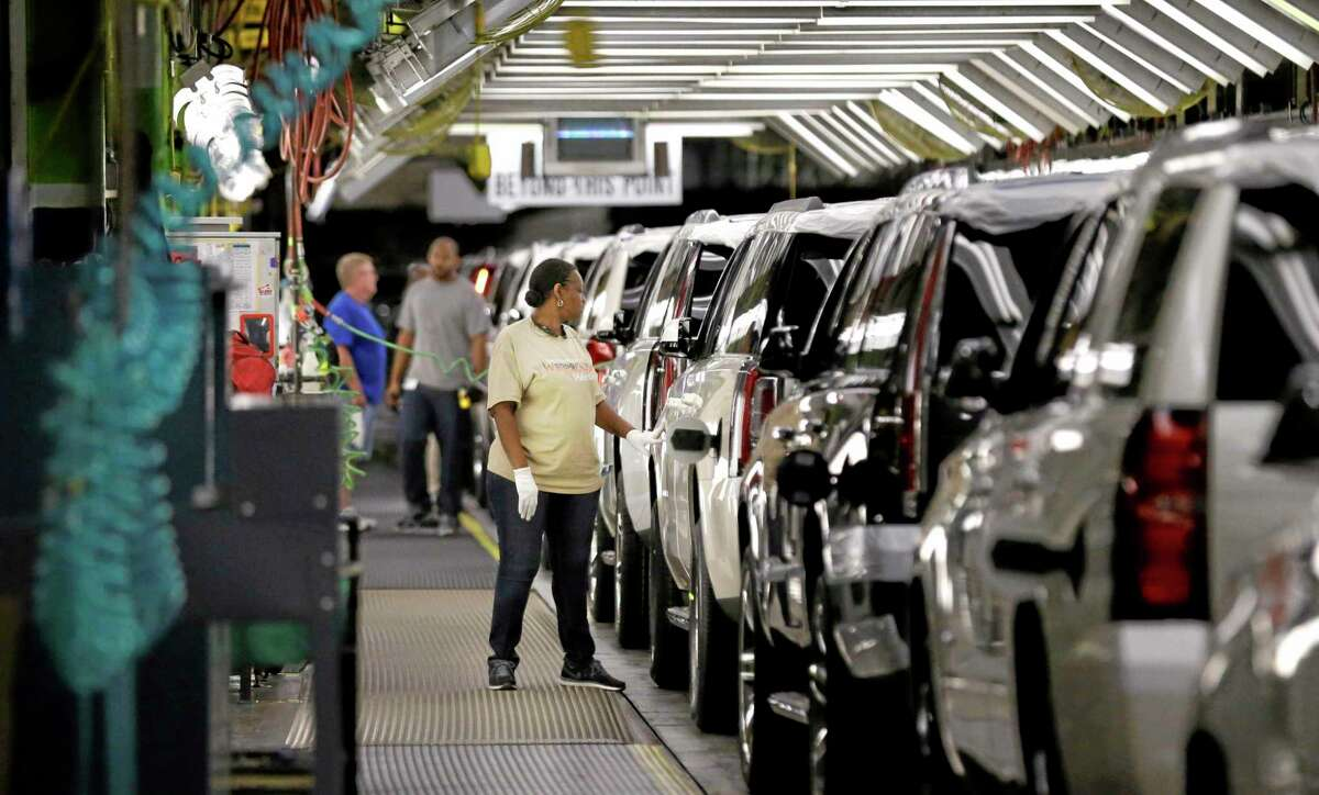In this May 13, 2014, file photo, an auto worker inspects finished SUVs coming off the assembly line at the General Motors auto plant in Arlington, Texas.