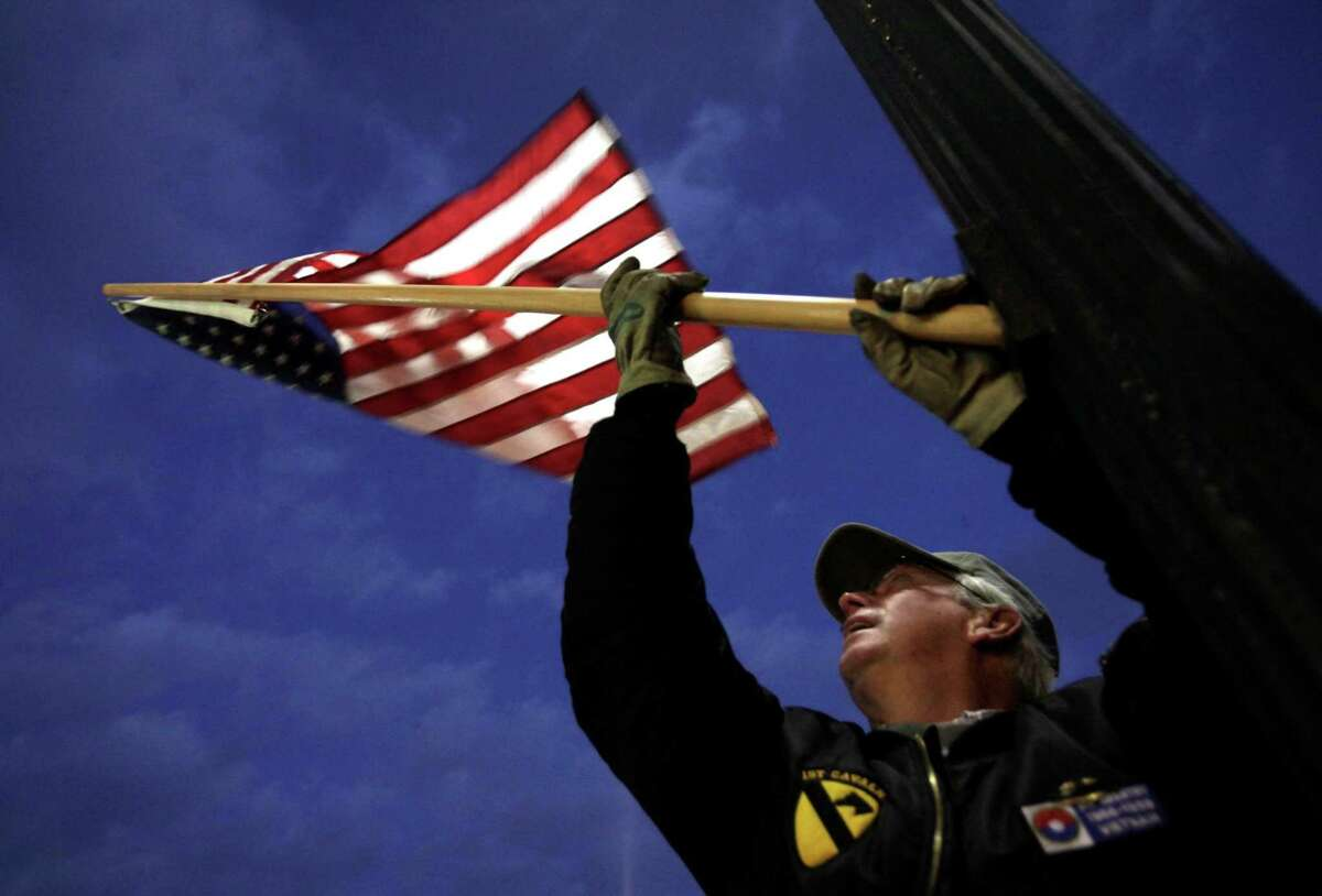 Vietnam War Veteran Steve Benner of American Legion Post 45 attaches an American flag to a light pole, on Veterans Day, Friday, Nov. 11, 2011, in Bowling Green, Ohio. Benner and a group of Veterans placed 48 flags along downtown streets. (AP Photo/Sentinel-Tribune, J.D. Pooley) MANDATORY CREDIT, TOLEDO BLADE OUT