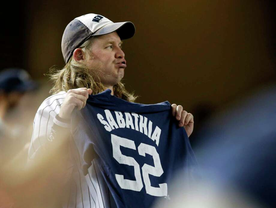 A Yankees fan holds a CC Sabathia shirt in the ninth inning Tuesday night in New York. Photo: Kathy Willens — The Associated Press  / AP