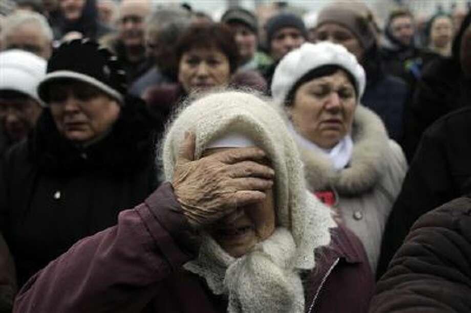 A woman reacts at a memorial for the people killed in clashes with the police at Kiev's Independence Square, the epicenter of the country's current unrest, Ukraine, Tuesday, Feb. 25, 2014. The Ukrainian parliament on Tuesday delayed the formation of a new government, reflecting political tensions and economic challenges following the ouster of the Russia-backed president. Parliament speaker Oleksandr Turchinov, who was named Ukraine's interim leader after President Viktor Yanukovych fled the capital, said that a new government should be in place by Thursday, instead of Tuesday, as he had earlier indicated. (AP Photo/Marko Drobnjakovic) Photo: AP / AP