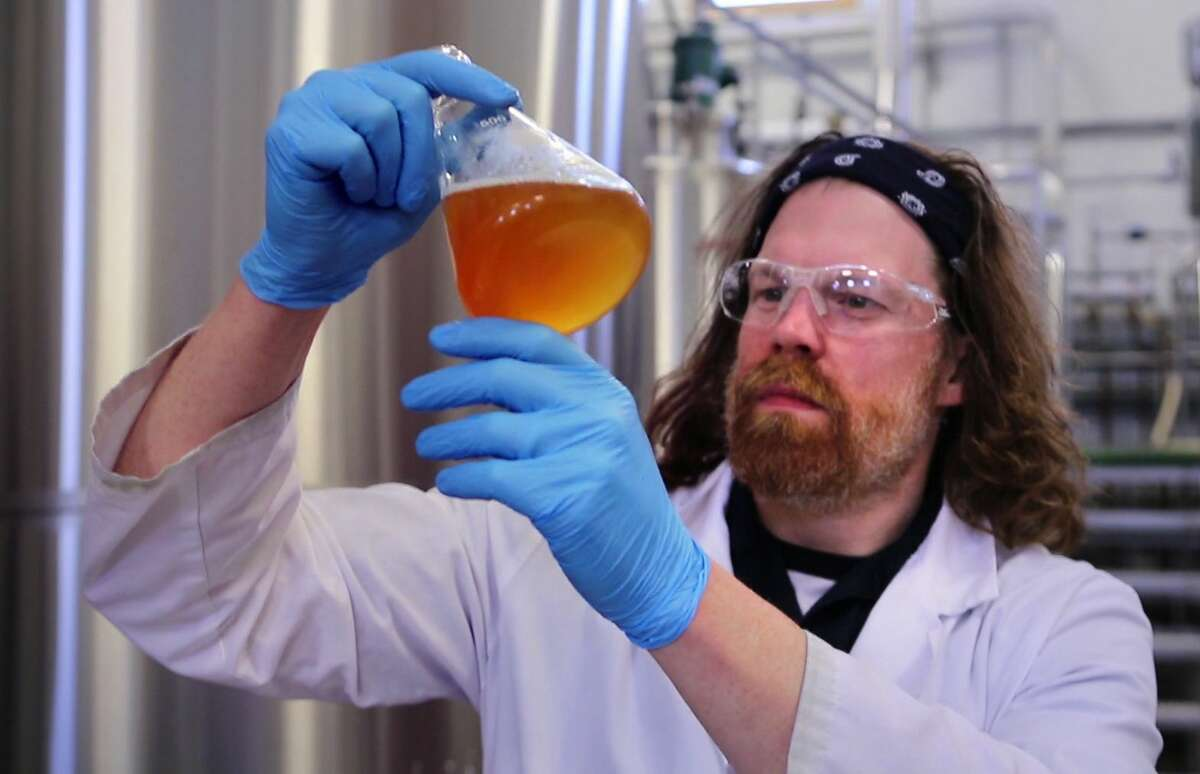 Dan Roberts, a quality control technician, examines a sample a beer taken from a fermenter at the Maine Beer Company in Freeport, Maine.