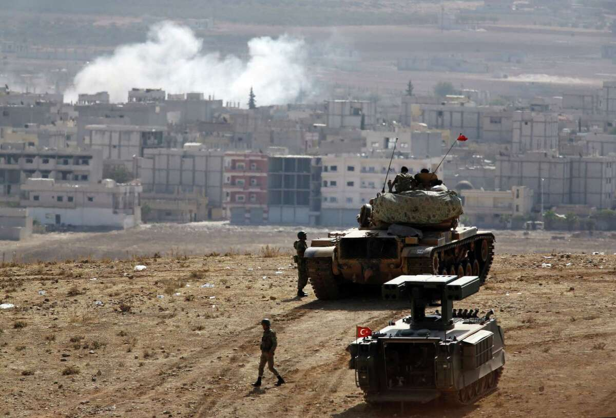 Turkish soldiers stand with a tank and an armoured vehicle as they hold their positions on a hilltop in the outskirts of Suruc, Turkey, at the Turkey-Syria border, overlooking smoke rising from a strike in Kobani, Syria, during fighting between Syrian Kurds and the militants of Islamic State group on Thursday.