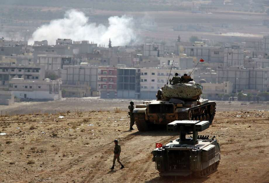 Turkish soldiers stand with a tank and an armoured vehicle as they hold their positions on a hilltop in the outskirts of Suruc, Turkey, at the Turkey-Syria border, overlooking smoke rising from a strike in Kobani, Syria, during fighting between Syrian Kurds and the militants of Islamic State group on Thursday. Photo: AP Photo  / AP