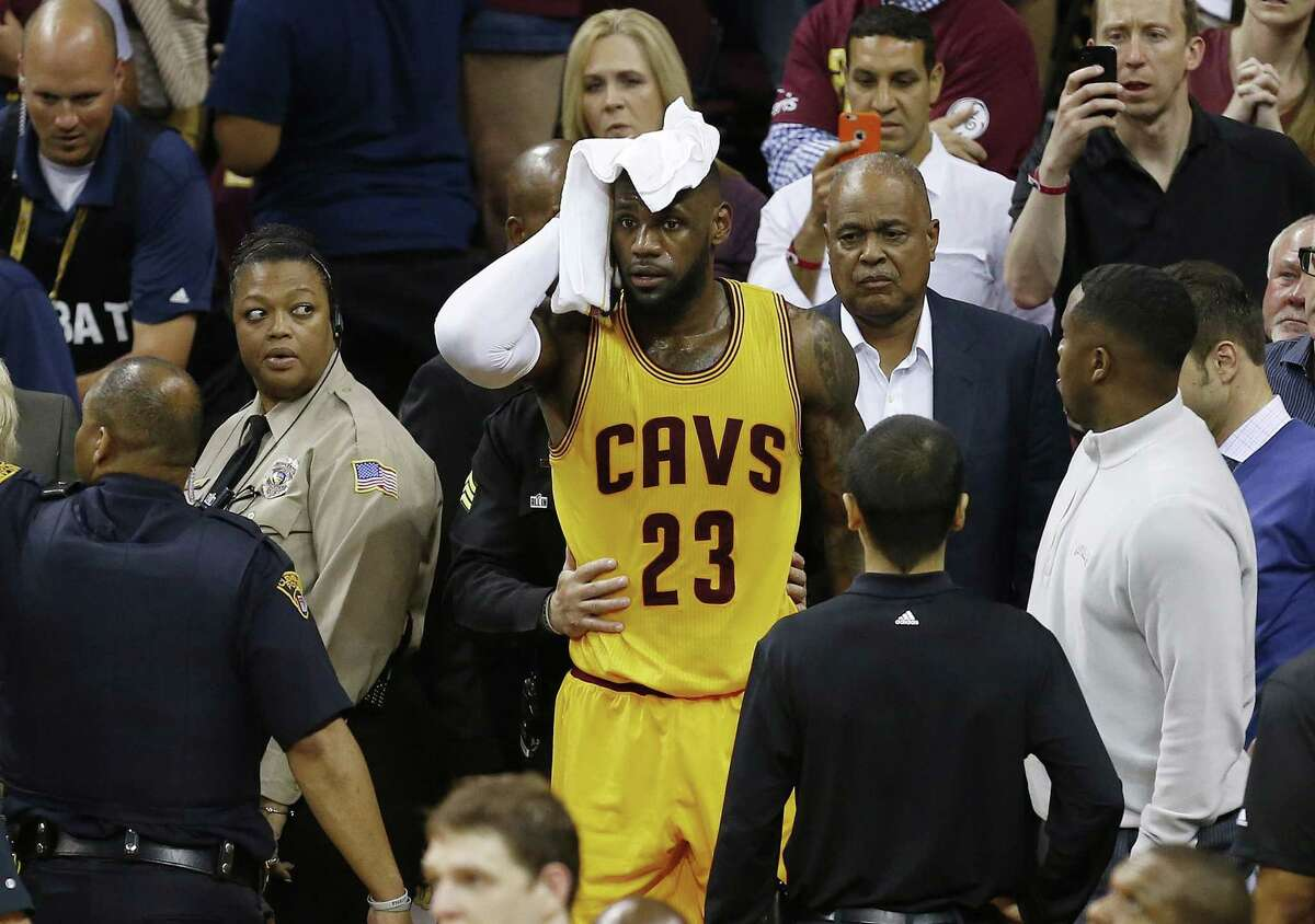The Cavaliers' LeBron James holds a towel to his head after being knocked into the fans during Game 4 of the NBA Finals against the Golden State Warriors. The Warriors won 103-82.