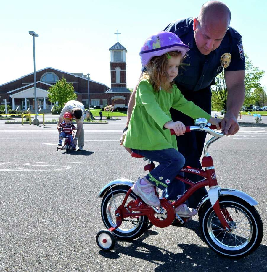 Upper Gwynedd Police Officer Bob Pro leads Clare Finley, 3, through a course during a free Family Bike Saftey Rodeo event in this file photo from The Reporter. Photo: The Reporter File Photo
