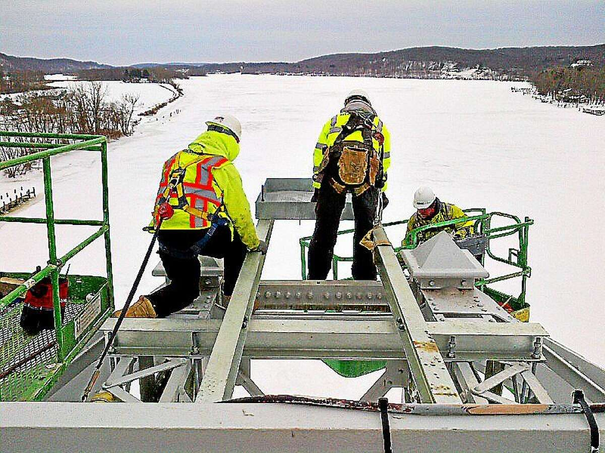 Workers perch on top of the bridge in freezing temps to secure the nesting platform in East Haddam.