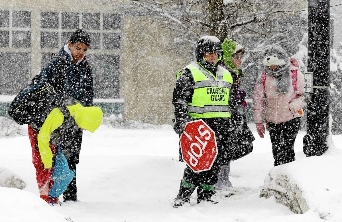 Students wait to cross the street during a heavy snow day in Glenview, Ill., Monday, Feb. 17, 2014.
