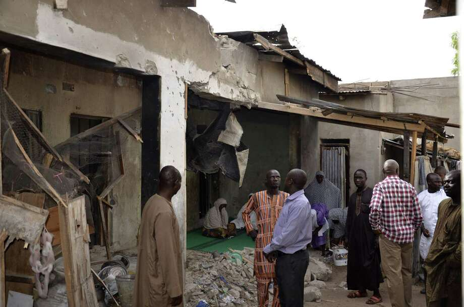 People inspect houses damaged damaged in Saturday's rocket propelled grenades by Islamic extremist in Maiduguri, Nigeria, Sunday, May 31, 2015. A bomb injured four people in a market Sunday in Maiduguri, a day after the northeastern Nigerian city was hit by a suicide bomber who killed 16 in a mosque. (AP Photo/Jossy Ola) Photo: AP / AP